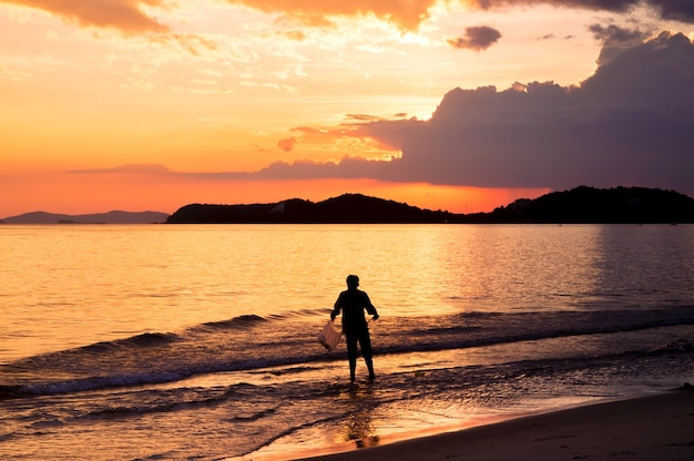 Silhouette of lonely man walking in to the sea at sunset