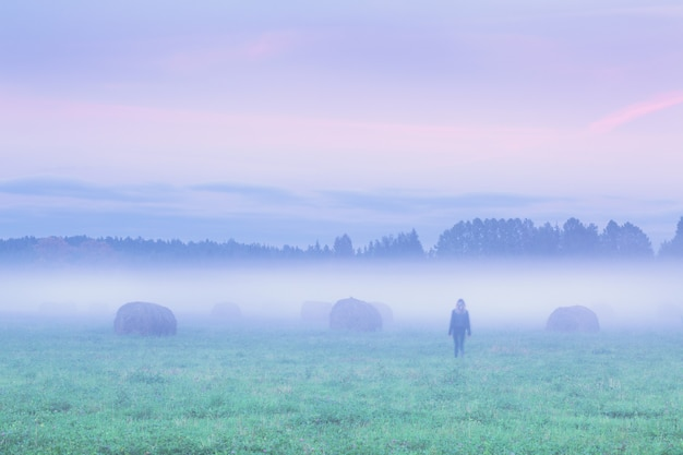 Silhouette of a lonely woman walking away in foggy field with haystacks at sunset