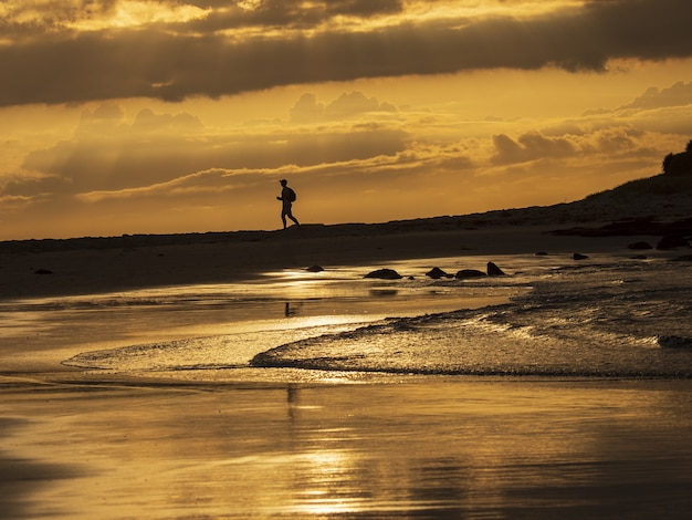 Silhouette of a male running on the rocky shore of the sea under the golden sunset sky