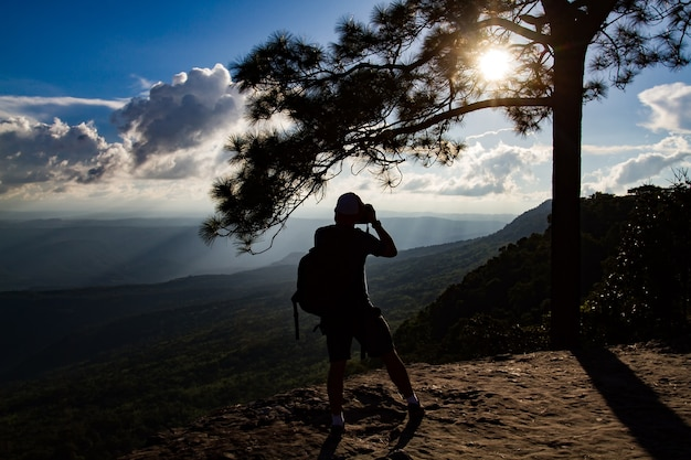 Silhouette a man asia with backpack taking a photo on the top of mountains ,soft focus