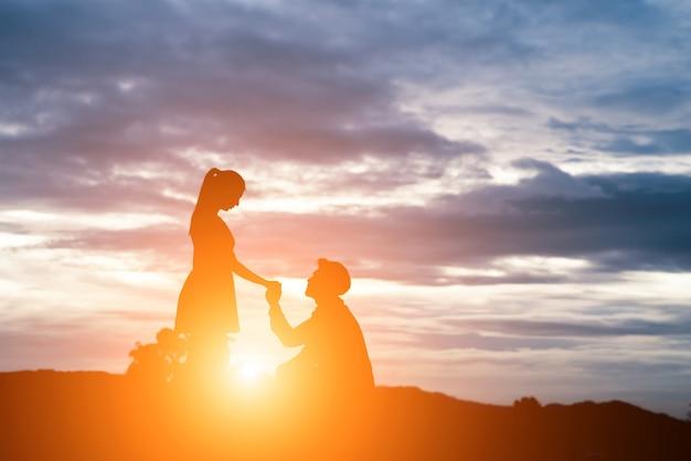 Sagoma di uomo chiedere donna di sposarsi su sfondo di montagna.
