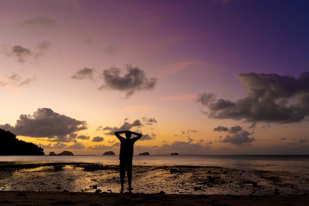 Silhouette of a man on the beach at sunset. man rejoices meets the sunset