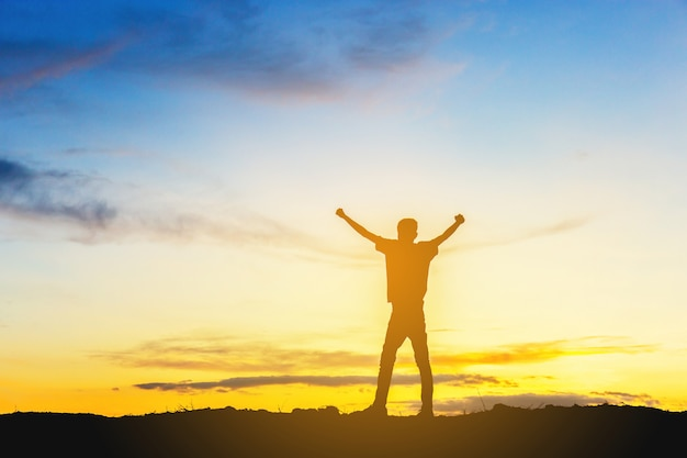Silhouette of man celebration success happiness on a mountain top evening sky sunset background.