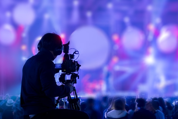 Silhouette of man covering event on stage with video camera
