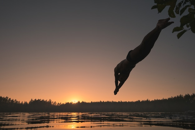 Silhouette of a man diving into a lake at sunset.