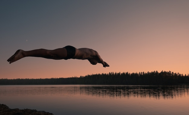Silhouette of a man diving into a lake at sunset