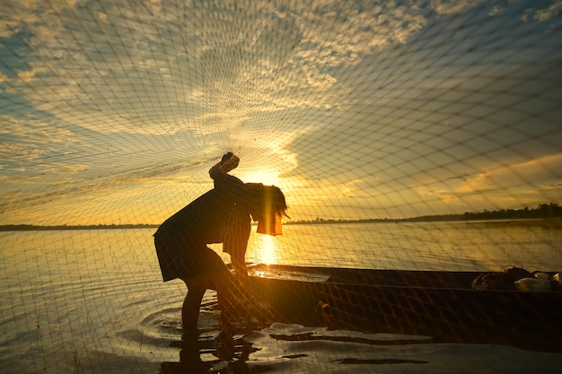 Silhouette of a man doing traditional thai traditional fishing in the river. in chiang mai, thailand 12/05/2021