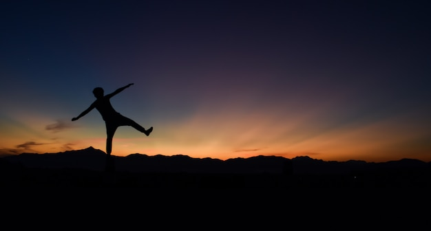 Silhouette of man doing walking at sunset