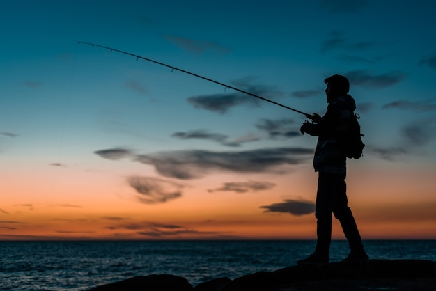 Silhouette of a man fishing at the beach at sunset