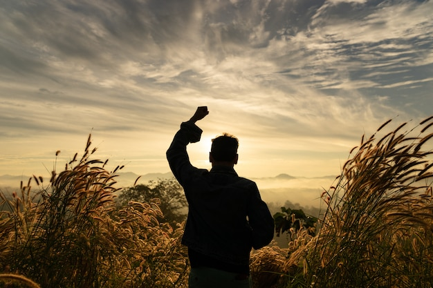 Silhouette man happy standing  with hands rise up on mountain with sunrise sky.