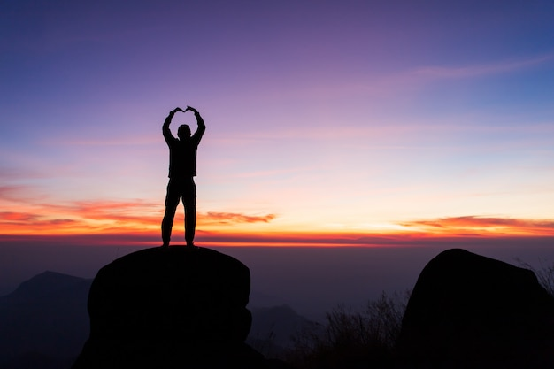 Silhouette of man hold up hands on the peak of mountain,success concept