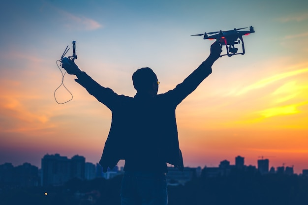 Silhouette of man holding switched on drone quad copter and remote control enjoying freedom victory
