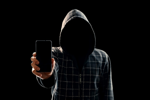 Silhouette of a man in a hood on a black background his face is not visible the hacker is holding the phone in his hands