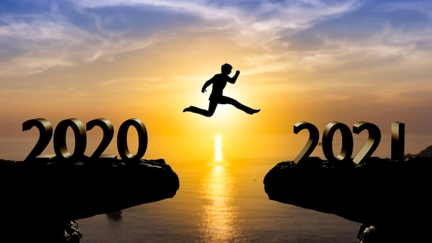 Silhouette man jump between 2020 and 2021 years with sunset wall,year 2021 concept