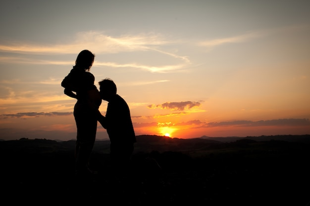 Silhouette of man kissing the belly of a mother on sunset