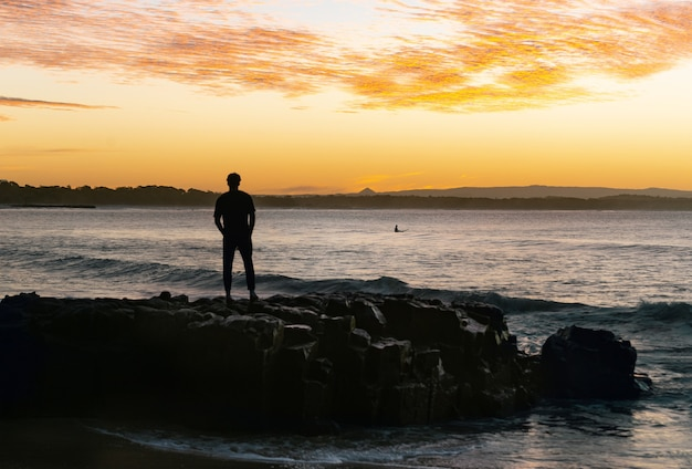 Silhouette of man looking the sunset standing on rock close to the ocean.noosa,queensland,australia
