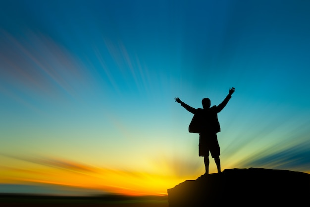 Silhouette of man on mountain top over sky and sun light success, leadership and people concept