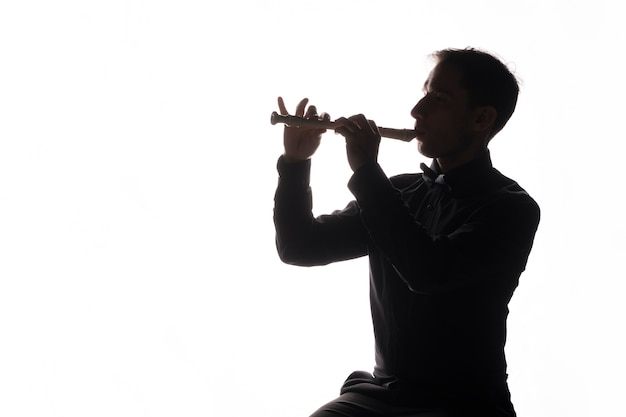 Silhouette of a man playing the flute