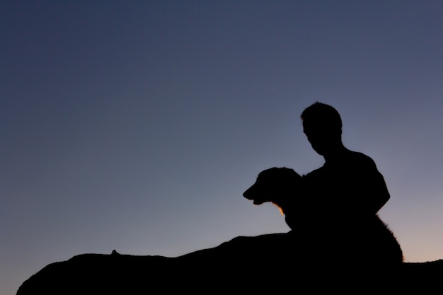 Silhouette of man playing with his dog at sunset. backlight. copy space.