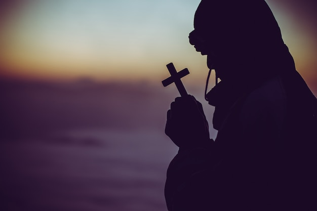 Silhouette of a man praying with a cross in hand at sunrise.