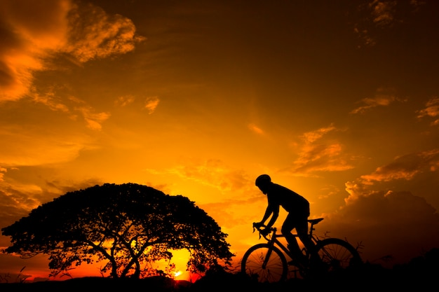 Silhouette man riding uphill with bicycle at sunset with orange sky in countryside.