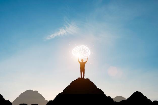 Силуэт человека поднимает руку вверх и держит виртуальный мозг на вершине горы с голубым небом. умное мышление и концепция идеи.