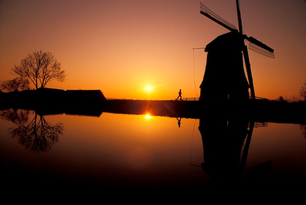 Silhouette of  man running and old-fashioned, wooden windmills along canal with yellow setting sun in background
