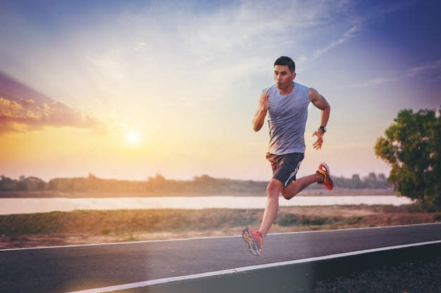 Silhouette of man running sprinting on road. fit male fitness runner during outdoor workout