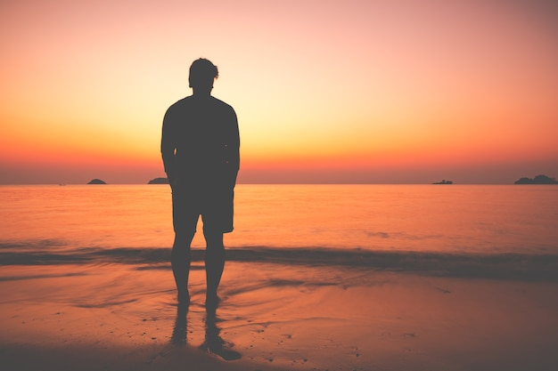 The silhouette of man sitting alone at the beach