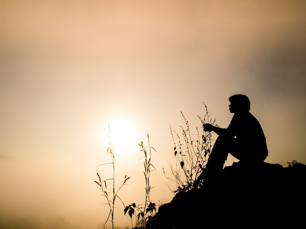 Silhouette of man sitting on a cliff at sunrise.