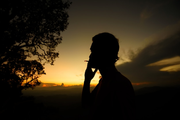 Silhouette of man smoking cigarette on the sunset