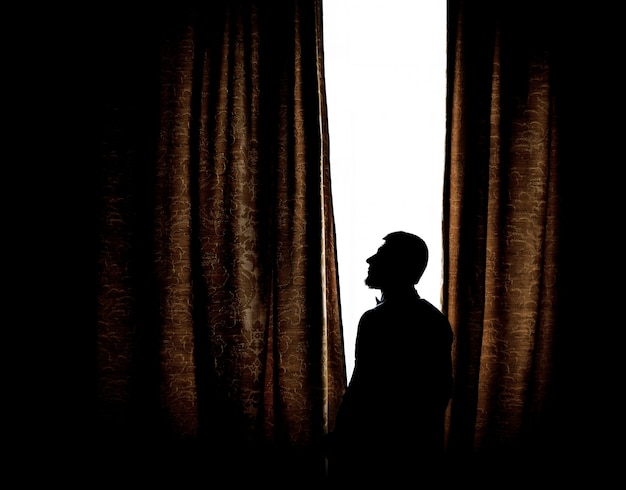 Silhouette of a man standing before a bright window