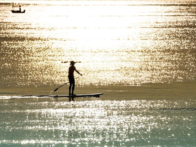 물 표면에 아침 햇빛 반사와 함께 잔잔한 바다에 패들 보드에 서 있는 실루엣 남자, 여름에 휴식