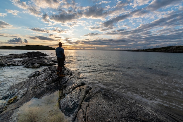 Silhouette of man standing on a rock and looking over sea toward the evening sun.