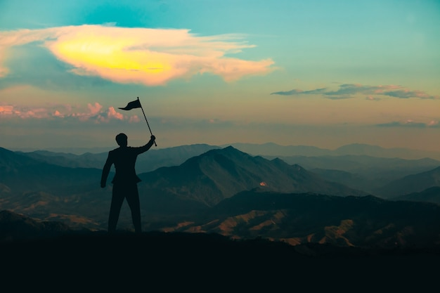 Silhouette of a man standing with a victory flag on the top of the mountain on sunrise sky background,business, success, leadership and achievement concept