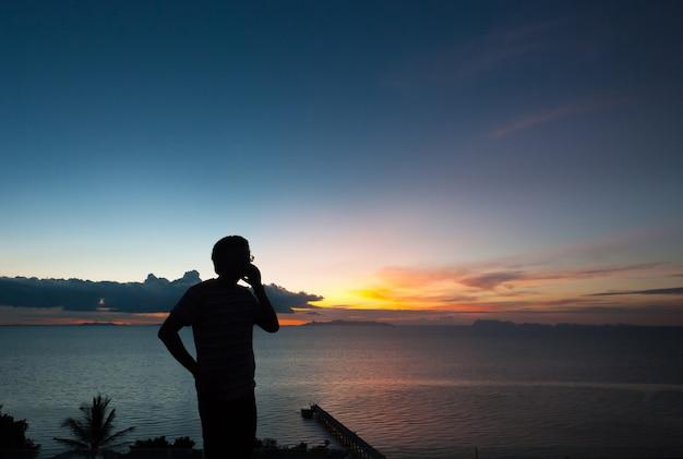 シルエットの男、電話で話す、日没の眺め。