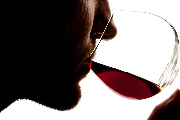 Silhouette of man tasting alcohol. isolated on white