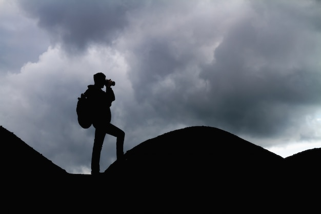 Silhouette of a man with backpack in the mountains is taking pictures of the landscape