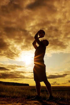 Silhouette of a man with a ball.
