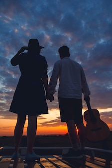 Silhouette of man with guitar and woman in a hat stand on roof of a car on background of the sunset