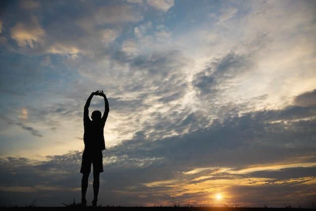 Silhouette of a man with hands raised in the sunset.
