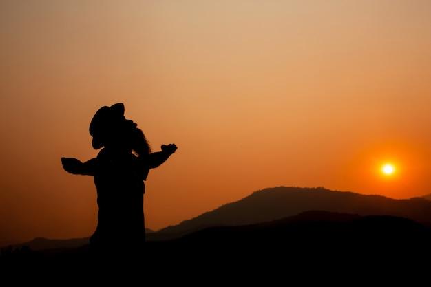 Silhouette di un uomo con le braccia aperte.