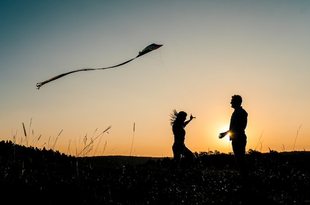 Silhouette of man and woman launching kite on nature