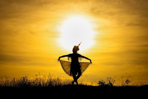 タイ南部の日没でシルエットmanohra女性が踊ります。