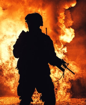 Silhouette of modern infantry soldier, elite army fighter in tactical ammunition and helmet, standing with assault service rifle in hands