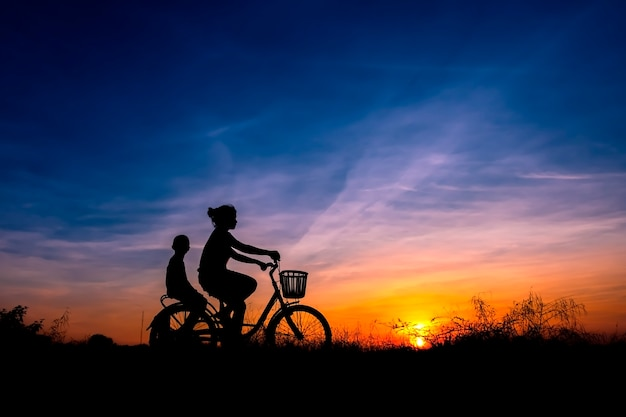 Silhouette of mom and kids cycling in sunset background.