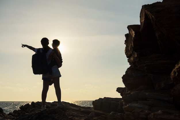 Silhouette mom and son look at view of sea and sunset on natural stone arch. happy family at khao laem ya national park, rayong, thailand. famous travel destination and holiday vacation in summer