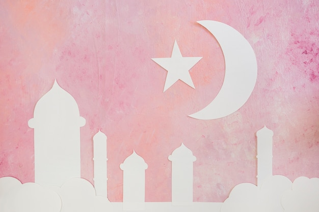Silhouette of mosque towers and crescent on pink