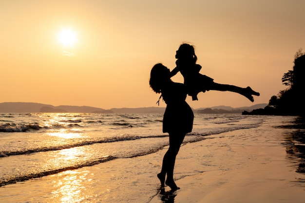 Silhouette of mother and child playing on the beach at sunset.