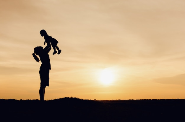 Silhouette of mother and daughter lifting child in air over scenic sunset sky at riverside